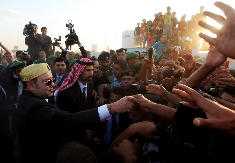 Morocco's King Mohammed VI shakes hands with Syrian refugees at Zaatari camp in Jordan during a trip to promote reforms  and regional security with Gulf countries and Jordan.