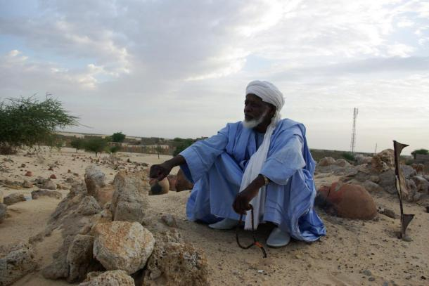 Man prays beside the remains of tombs of locally venerated Islamic saints, whose mausoleums were destroyed by Islamist group Ansar Dine, in Timbuktu, Mali (AP)