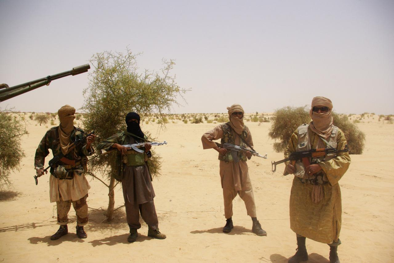 Ansar Dine fighters stand guard during a hostage handover in the desert outside Timbuktu, Mali (AP)