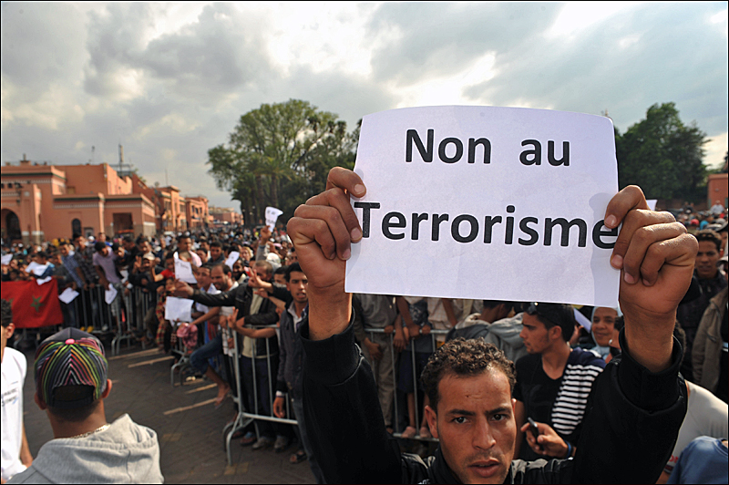 "A man holds a poster reading ""No to terrorism"" as he gathers at the site of the 2011 Marrakech bomb attack. [AFP/Abdelhak Senna]"