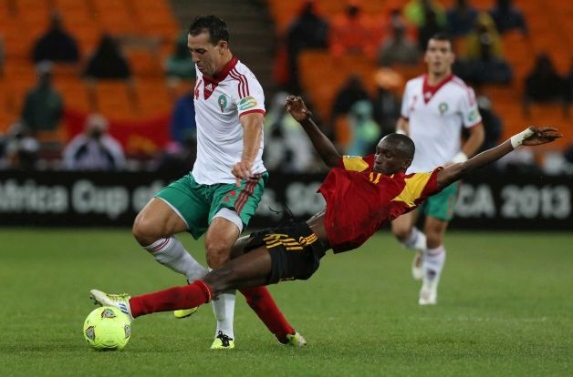 Morocco's Mounir El Hamdaoui, left, is challenged by Angola's Dede de Carvalho, center, during their African Cup of Nations group A soccer match at Soccer City stadium in Soweto, South Africa, Saturday Jan. 19, 2013. Photo: Themba Hadebe