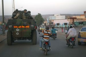Motorcyclist to French troops in armored personnel carriers in Mali's capital Bamako on their way to engage al-Qaeda-linked forces around Mopti. (AP)
