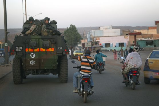 Motorcyclist waves support as French troops in two armored personnel carriers drive through Mali's capital Bamako on the road to Mopti Jan. 15. French forces led an all-night aerial bombing campaign Tuesday to wrest control of a small Malian town from armed Islamist extremists. (AP)