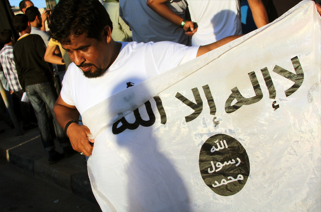"A Benghazi man holds an al-Qaeda flag during a 2012 ""pro-Sharia"" rally. Security experts say the jihadists who fled Mali have relocated to Libya. [AFP/Abdullah Doma]"
