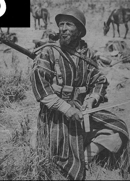 "Originally pictured in Yank magazine with the caption: ""A colorful Goum sharpens an American bayonet. His rifle is also American, his helmet, French."""